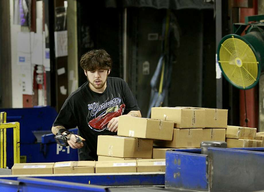 Carlos Nava, above, got his FedEx Ground job in the holiday hiring frenzy. Below, the package sorting facility gets busy. Photo: Brant Ward, The Chronicle