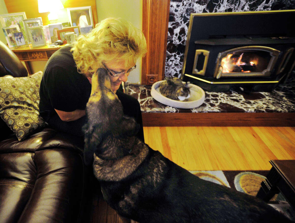 Maureen Walsh lets her dog, Buddy, lick her cheek while at home in Danbury on Tuesday, Dec. 4, 2012. Buddy stayed with his dead owner for five weeks and was recently adopted by the Walshes.