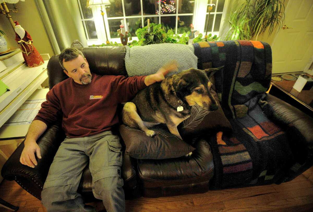 Brendan Walsh pets his dog, Buddy, while at home in Danbury on Tuesday, Dec. 4, 2012. Buddy stayed with his dead owner for five weeks and was recently adopted by the Walshes.