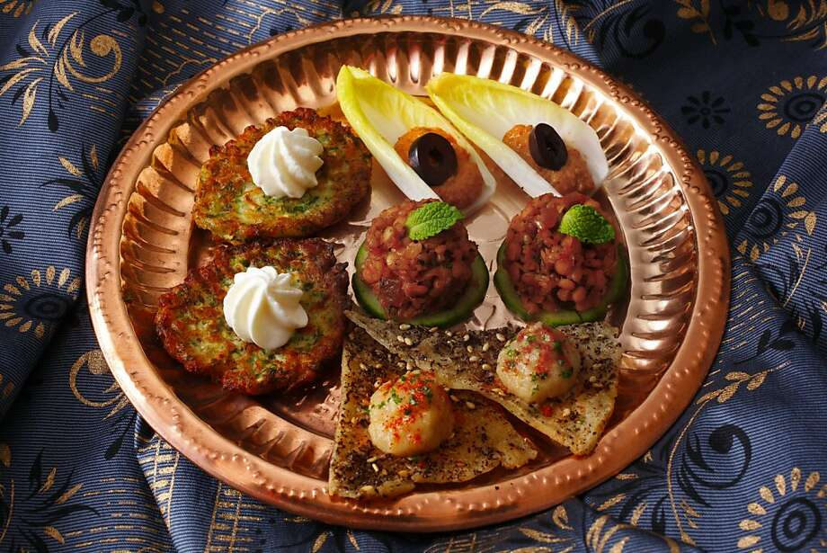 Turkish-themed holiday appetizer plate, clockwise from top: Muhammara Dip in Endive Leaves, Red Lentil, Mint & Bulgur Salad on Cucumber Rounds, charred Eggplant Spread on Za'atar Pita Triangles and Zucchini Feta Pancakes. Photo: Craig Lee, Special To The Chronicle