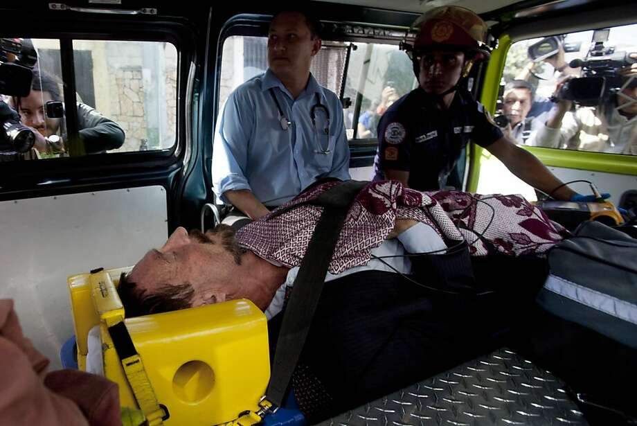 Software mogul John McAfee lies inside an ambulance before being taken to a hospital in Guatemala City. Photo: Moises Castillo, Associated Press