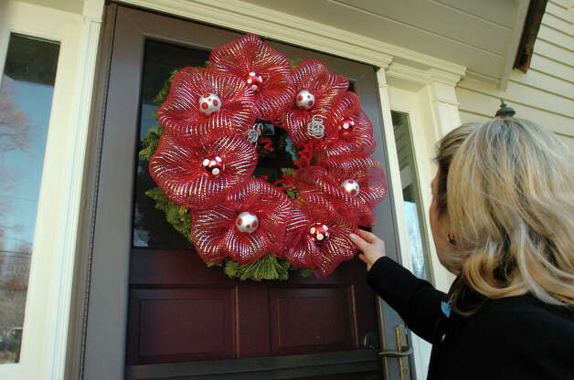 Patti Watkins takes a look at Soudi Salek's entry into the Shippan Point Garden Club's annual Doors of Shippan Christmas decoration contest in Stamford, Conn., Dec. 6, 2012. Photo: Keelin Daly / Stamford Advocate Riverbend Stamford, CT