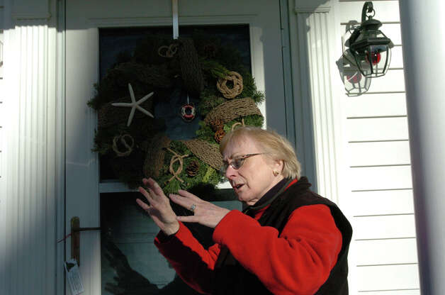 Robin Bughman discusses design while examining a wreath on Ocean Drive East in the Shippan Point Garden Club's annual Doors of Shippan Christmas decoration contest in Stamford, Conn., Dec. 6, 2012. Photo: Keelin Daly / Stamford Advocate Riverbend Stamford, CT