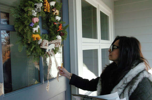 "Judge Soudi Salek looks over a wreath entered into the ""Newcomer"" division of the Shippan Point Garden Club's annual Doors of Shippan Christmas decoration contest in Stamford, Conn., Dec. 6, 2012. Photo: Keelin Daly / Stamford Advocate Riverbend Stamford, CT"