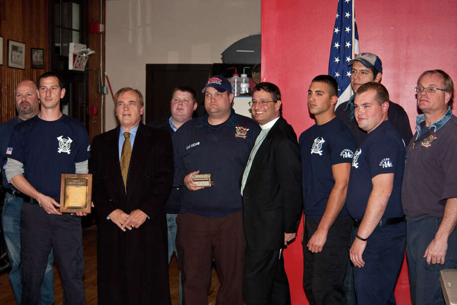 Trinity Episcopal Church recently gave a plaque to the Southport Fire Department to recognize the departmentâÄôs saving the church after Hurricane Sandy. Standing from left to right during a presentation ceremony are Todd Roberts, firefighter; Jon Leone, station president; John Morgan, the churchâÄôs senior warden; Michael Romsky, firefighter; Chris Luciani, station chief; the Rev, Nicholas T. Porter, the churchâÄôs rector; and firefighters Eric Pironto, Michael Bihary, Dan Torska and Ralph Arnone. Photo: Contributed Photo