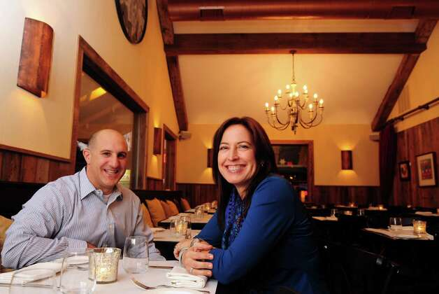 Greg Addonizio and wife Debra Ponzek, owners of Aux Delices Bistro in Westport, Conn., sit in the dining room of their quaint restaurant. Photo: Autumn Driscoll / Connecticut Post