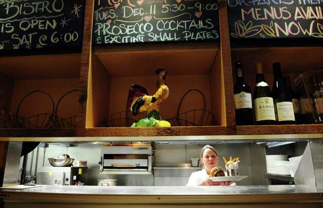 Chef Lisa Varnberg puts up an order at Aux Delices Bistro in Westport, Conn. Photo: Autumn Driscoll / Connecticut Post