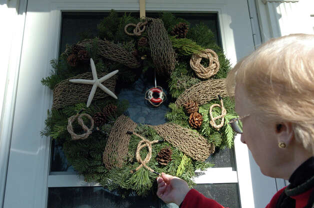 Robin Bughman examines the design of a wreath on Ocean Drive East in the Shippan Point Garden Club's annual Doors of Shippan Christmas decoration contest in Stamford, Conn., Dec. 6, 2012. Photo: Keelin Daly / Stamford Advocate Riverbend Stamford, CT