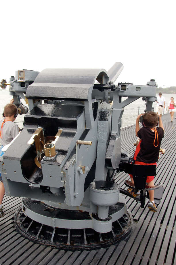 Children play on one of the deck guns of the sub nicknamed Pearl Harbor Avenger. (Jeanne Cooper / SFGate)