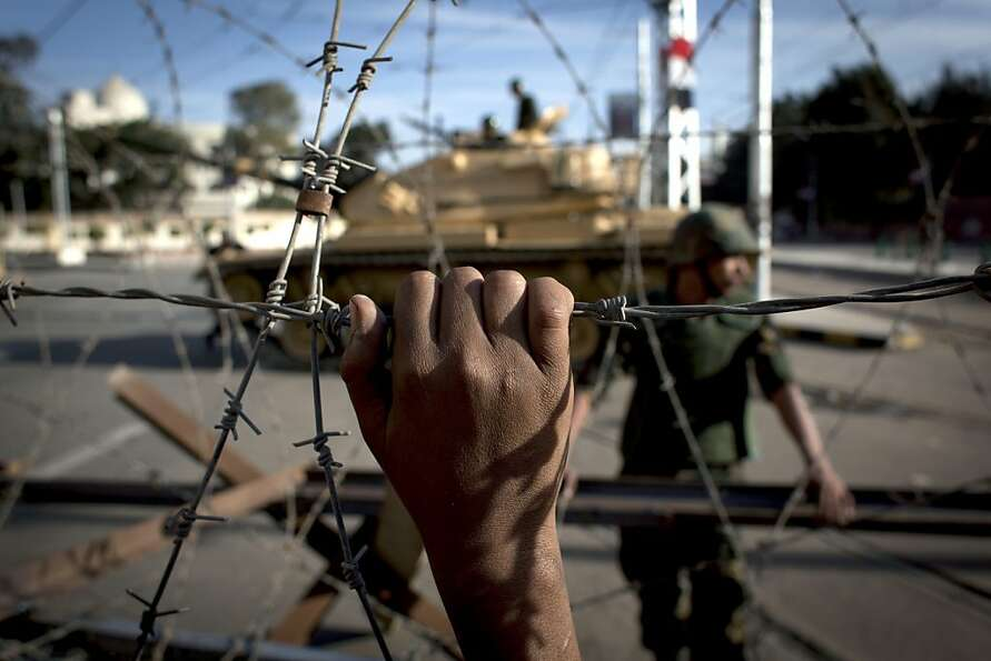 An Egyptian army tank is seen behind barbed wire securing the perimeter of the presidential palace w