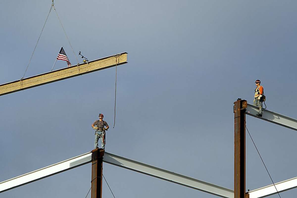 Steel workers wait as a signed I-beam is lifted into place at the highest point of the new 49ers stadium during the traditional Topping Off ceremony in Santa Clara, Calif., Thursday, December 6, 2012.