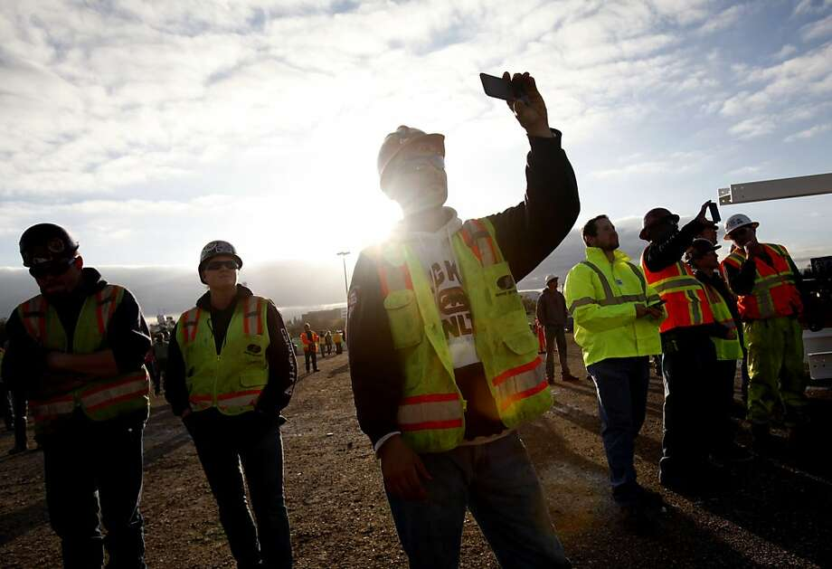 Steve Tougas (center) takes photos during the Topping Out ceremony, where a signed I-beam is added to the highest point of the new 49ers stadium in Santa Clara, Calif., Thursday, December 6, 2012. Photo: Sarah Rice, Special To The Chronicle