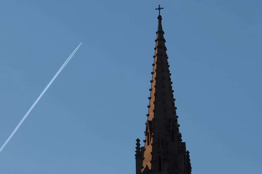 A jet flies above the north steeple of the Cathedral of the Immaculate Conception on Thursday, Dec. 6, 2012 in Albany, NY.  The north steeple contains the bells of the church, which will be played for the first time in many years.   (Paul Buckowski / Times Union) Photo: Paul Buckowski