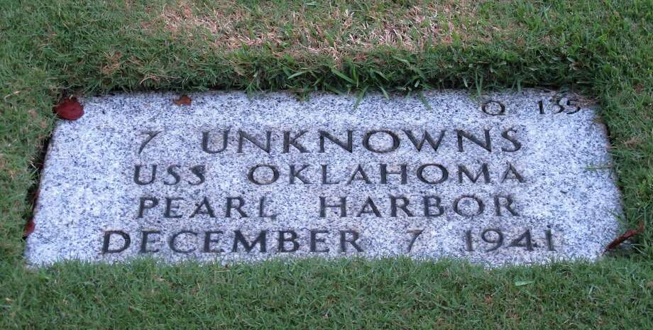 This Dec. 5, 2012 photo at the National Memorial Cemetery of the Pacific in Honolulu shows a gravestone identifying it as the resting place of 7 unknowns from the USS Oklahoma who died in Japanese bombing of Pearl Harbor. The Navy and National Park Service will honor Ray Emory, a Pearl Harbor survivor who pushed to put ship names on the gravestones and identify unknown remains, on Dec. 7 for his determination to have Pearl Harbor remembered, and remembered accurately. (AP Photo/Audrey McAvoy) Photo: Audrey McAvoy