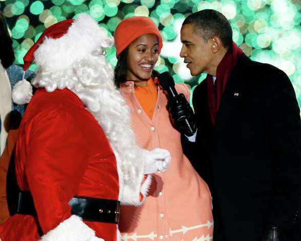 President Barack Obama, right, and daughter Malia Obama, sing as Santa Claus arrives during the 90th annual National Christmas Tree Lighting ceremony on the Ellipse south of the White House, Thursday, Dec. 6, 2012, in Washington. Photo: Alex Brandon, Associated Press / AP