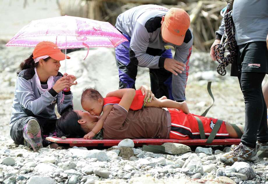 Lenlen Medrano and her child (on stretcher), survivors of Typhoon Bopha, prepare to be transported across a surging river on a zip line in the town of New Bataan, compostela province on December 6, 2012. Nearly 200,000 people are homeless and more than 300 dead after the Philippines suffered its worst typhoon this year, authorities said on December 6, reaching out for international aid to cope with the scale of the disaster. Photo: TED ALJIBE, AFP/Getty Images / AFP