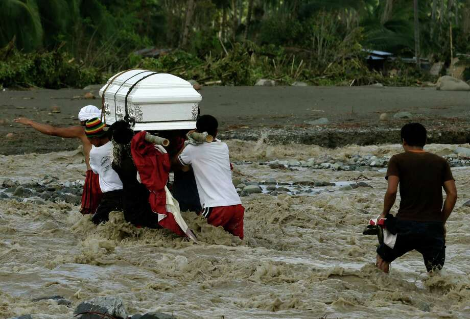 Relatives cross a river to bury their loved one, who died in a flash flood caused by Typhoon Bopha, Thursday, Dec. 6, 2012, in New Bataan township, Compostela Valley in the southern Philippines.  The powerful typhoon that washed away emergency shelters, a military camp and possibly entire families in the southern Philippines has killed hundreds of people with nearly 400 missing, authorities said Thursday. (AP Photo/Bullit Marquez) Photo: Bullit Marquez, Associated Press / AP