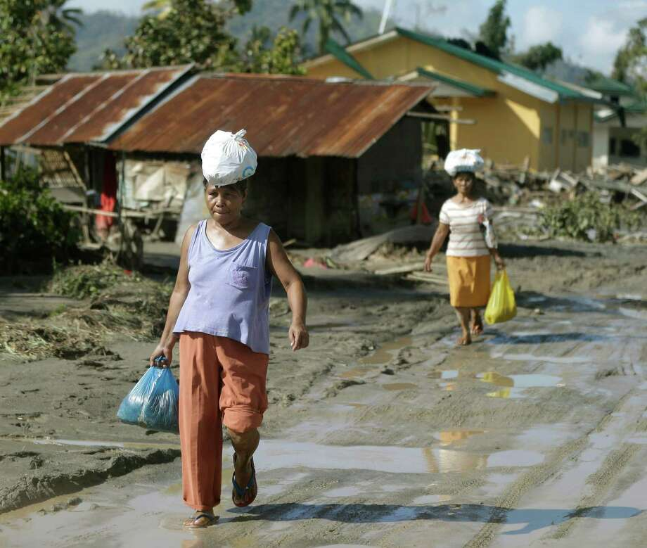 Residents, impacted by Tuesday's storm, walk back to their homes after receiving relief supplies Thursday, Dec.6, 2012, in New Bataan township, Compostela Valley in the southern Philippines.  The powerful typhoon that washed away emergency shelters, a military camp and possibly entire families in the southern Philippines has killed hundreds of people with nearly 400 missing, authorities said Thursday. (AP Photo/Bullit Marquez) Photo: Bullit Marquez, Associated Press / AP