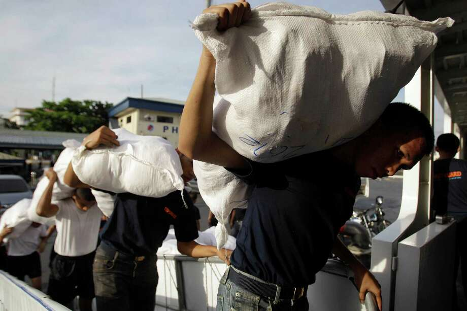Members of the Philippine Coast Guard carry relief goods for victims of flash floods caused by Typhoon Bopha in Davao province, while loading their ship in Manila, Philippines on Thursday, Dec. 6, 2012. The powerful typhoon that washed away emergency shelters, a military camp and possibly entire families in the southern Philippines has killed hundreds of people with nearly 400 missing, authorities said Thursday. (AP Photo/Aaron Favila) Photo: Aaron Favila, Associated Press / AP
