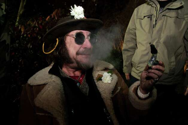 "A man known as ""Professor Gizmo,"" smokes marijuana in a glass pipe, Wednesday, Dec. 5, 2012, just before midnight at the Space Needle in Seattle. Possession of marijuana became legal in Washington state at midnight, and several hundred people gathered at the Space Needle to smoke and celebrate the occasion, even though the new law does prohibit public use of marijuana. (AP Photo/Ted S. Warren) Photo: Ted S. Warren"