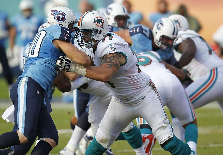 Miami Dolphins tackle Jake Long, second from left, blocks Tennessee Titans defensive end Scott Solomon during the second half of an NFL football game, Sunday, Nov. 11, 2012 in Miami. The Titans defeated the Dolphins 37-3. (AP Photo/Wilfredo Lee) Photo: Wilfredo Lee, Associated Press