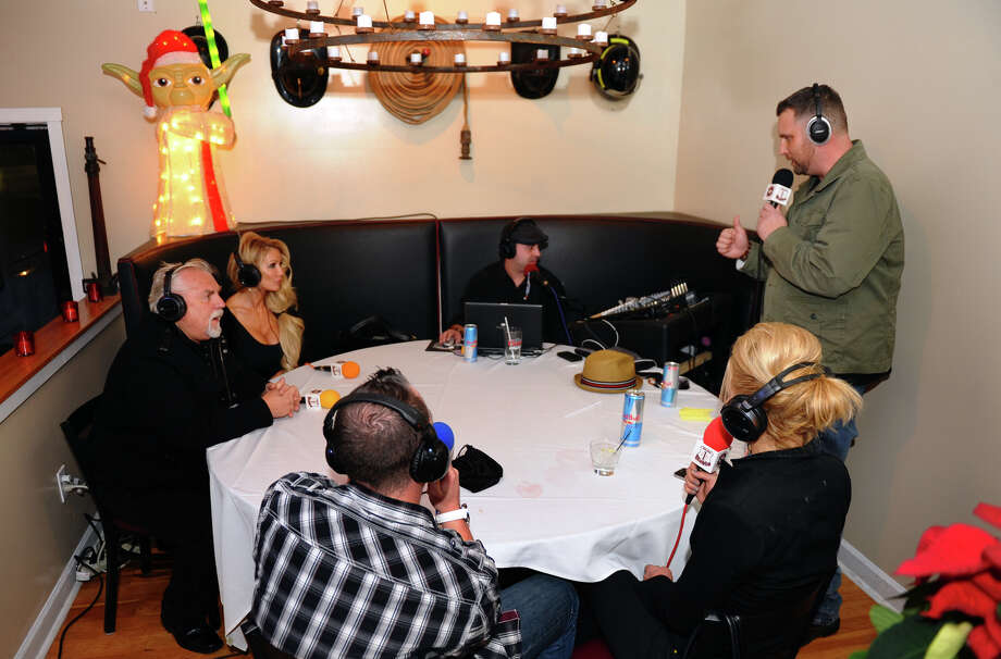 Black Rock native John Ratzenberger and his wife Julie, at left, take part in a live broadcast of the Modern Problems Radio Show at the Fire Engine Pizza Company restaurant on Fairfield Avenue in the Black Rock section of Bridgeport, Conn. on Thursday December 6, 2012. Interviewing Ratzenberger at right is host Davey Love. Photo: Christian Abraham / Connecticut Post