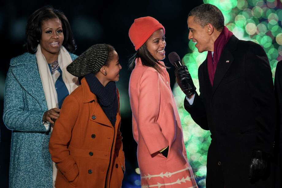 US First Lady Michelle Obama, daughters Sasha and Malia Obama and US President Barack Obama sing Santa Clause is Coming to Town during the 90th annual National Christmas Tree Lighting on the Ellipse of the National Mall December 6, 2012 in Washington, DC. Obama and others attended the event which included entertainment before the lighting of the National Christmas Tree. Photo: BRENDAN SMIALOWSKI, AFP/Getty Images / 2012 Brendan Smialowski