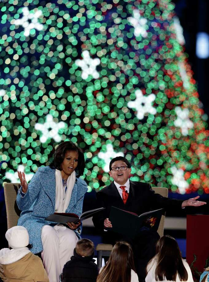 "First lady Michelle Obama, left, and Rico Rodriguez, read ""The Night Before Christmas"" to children during the 90th annual National Christmas Tree Lighting ceremony on the Ellipse south of the White House, Thursday, Dec. 6, 2012 in Washington. Photo: Alex Brandon, Associated Press / AP"