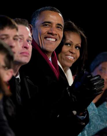 President Barack Obama and first Lady Michelle Obama look to the stage during the National Christmas Tree Lighting on the Ellipse, Thursday, Dec. 6, 2012, in Washington. This year's giant blue spruce is new, transplanted in October on the Ellipse, south of the White House. Photo: Carolyn Kaster, Associated Press / AP