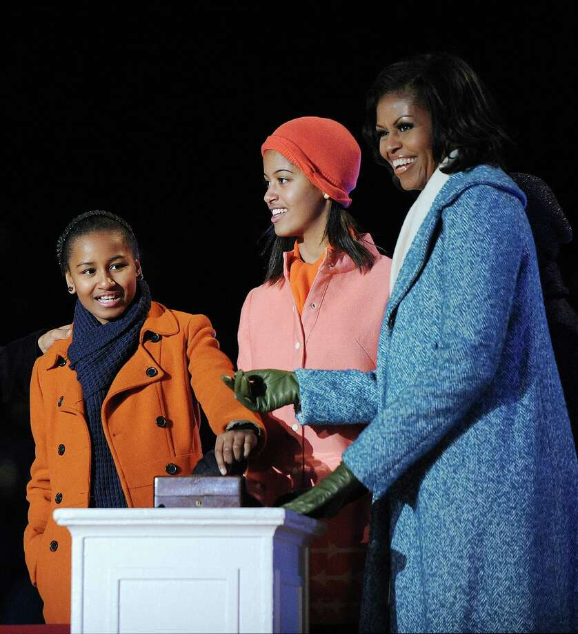 First lady Michelle Obama (R) and their daughters Malia (C) and Sasha Obama light the 90th National Christmas Tree during the Lighting Ceremony on the Ellipse behind the White House on December 6, 2012 in Washington, DC. This year is the 90th annual National Christmas Tree Lighting Ceremony. Photo: Pool, Getty Images / 2012 Getty Images