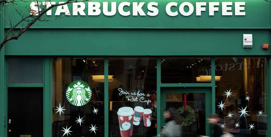 "FILE - This is a Monday, Dec.  3, 2012 file photo  pedestrians walk past a branch of the Starbucks shop chain in west  London.  Starbucks bowed to mounting pressure over its tax affairs in Britain and revealed Thursday Dec. 6, 2012  that it would pay about 10 million pounds ($16 million) in each of the next two years. Having been slammed by the country's lawmakers of ""immorally"" avoiding tax, Starbucks' U.K. managing director Kris Engskov said the firm had agreed to pay more than required by law. ""With the backdrop of these difficult times, in the area of tax, our customers clearly expect us to do more,"" he told the London Chamber of Commerce.(AP Photo/Alastair Grant, File) Photo: Alastair Grant"