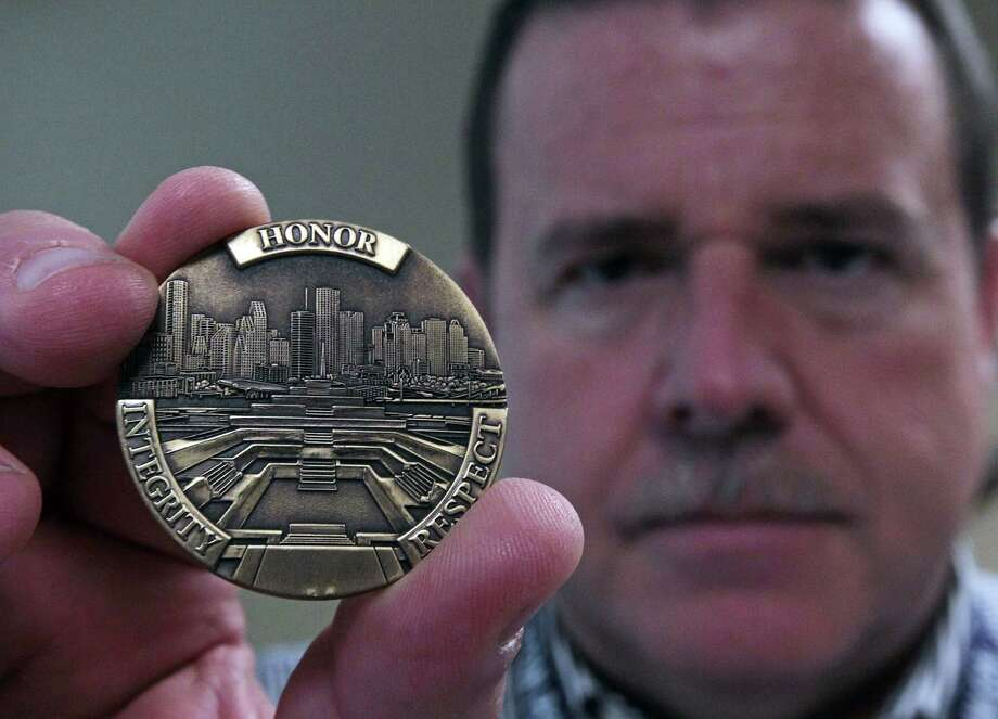 "Houston Police Officers Union President Ray Hunt shows a ""Challenge Coin."" Chief Charles McClelland's department paid $33,950 for the 7,700 coins and requires all HPD officers to carry them. Photo: James Nielsen, Staff / © Houston Chronicle 2012"