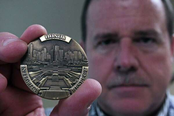 Chief, and a large brass coin, remind police of their duty