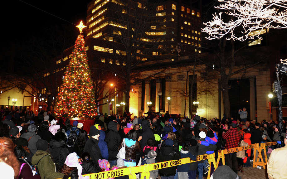 After a countdown, people turn to watch as the tree lights are turned on, during the annual Downtown Holiday Tree Lighting at McLevy Green in downtown Bridgeport, Conn. on Thursday December 6, 2012. Photo: Christian Abraham / Connecticut Post