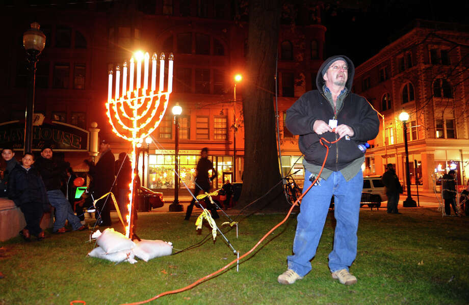 Public Works employee John Tristine lights up the menorah for Hanukkah at the annual Downtown Holiday Tree Lighting at McLevy Green in downtown Bridgeport, Conn. on Thursday December 6, 2012. Photo: Christian Abraham / Connecticut Post