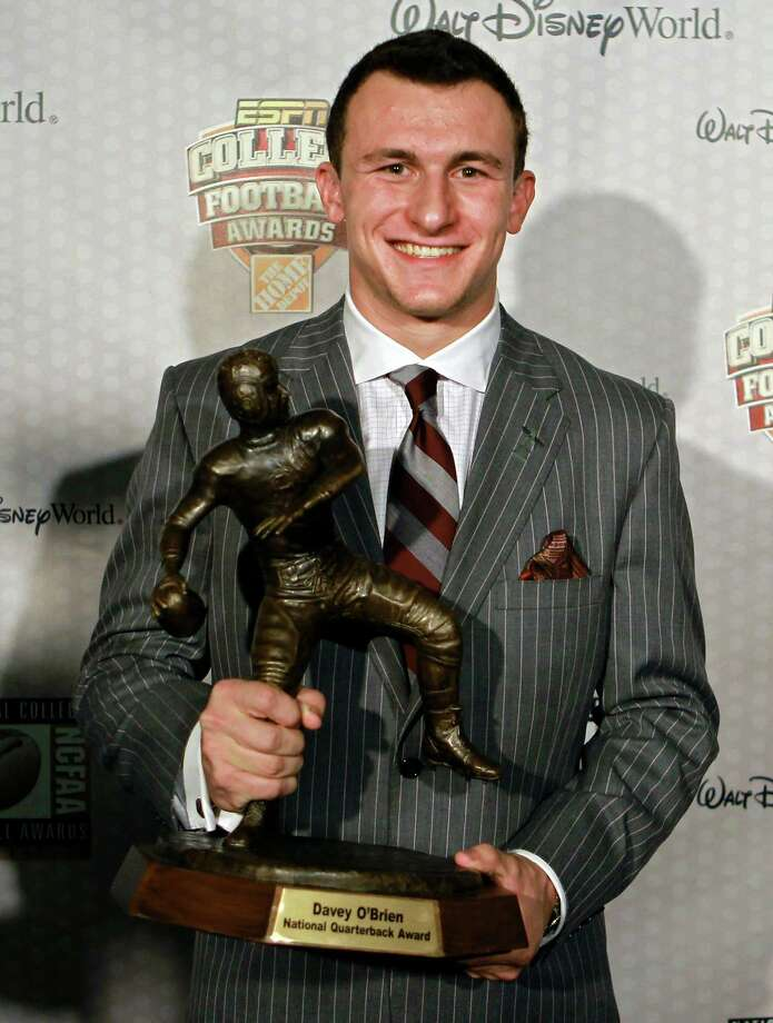 Texas A&M quarterback Johnny Manziel  displays his trophy for the Davey O'Brien Award after being named the nation's best quarterback at the Home Depot College Football Awards in Lake Buena Vista, Fla., Thursday, Dec. 6, 2012. (AP Photo/John Raoux) Photo: John Raoux, Associated Press / AP