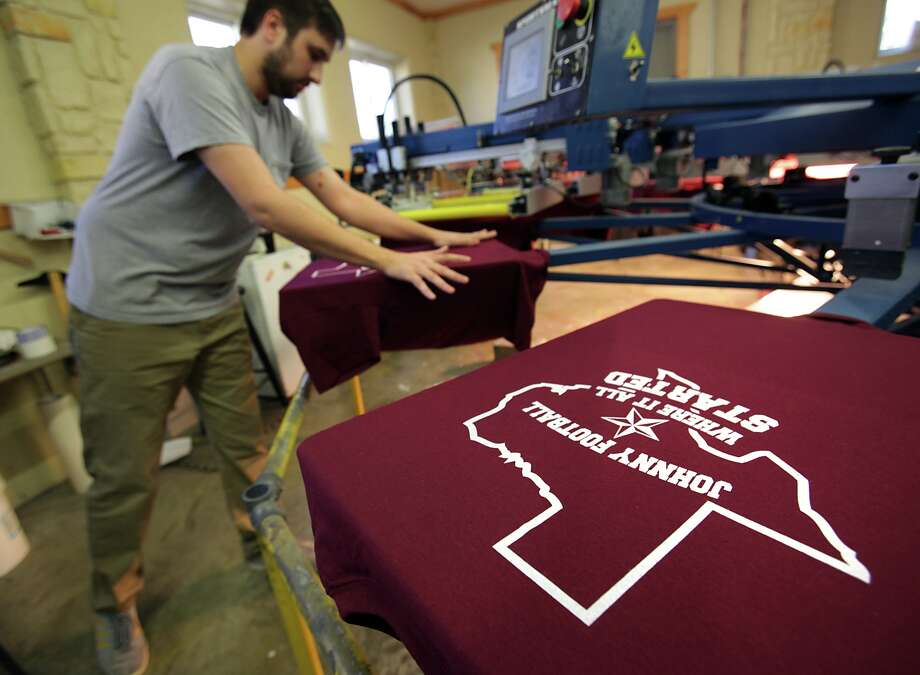 Scott Klingle of San Saba Cap in Kerrville, Tx, smooths out a t-shirt on a machine printing t-shirt for Wing King Restaurant, to be used in promotions Saturday night during a Heisman Trophy Awards watching party. Hometown football hero Johnny Manziel, who attended Tivy High School, is a candidate for the Heisman Trophy. Photo: Bob Owen, San Antonio Express-News / © 2012 San Antonio Express-News