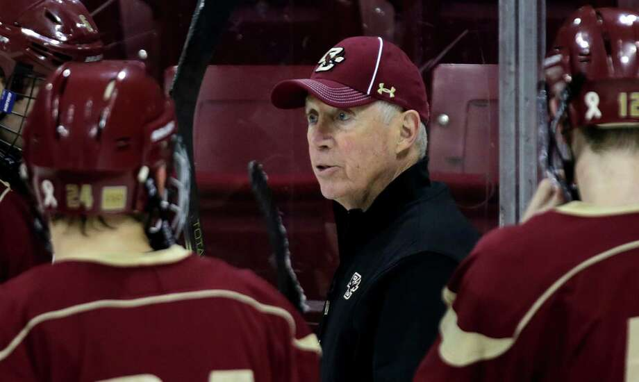 In this photo taken Dec. 5, 2012, Boston College hockey coach Jerry York, center, talks with his players during an NCAA college hockey practice in Boston. With 924 career victories, York is tied with Ron Mason atop college's all-time win list. He tied the longtime Michigan State coach by defeating rival Boston University last weekend, and he could break the record if the Eagles win in Providence on Friday night. (AP Photo/Charles Krupa) Photo: Charles Krupa / AP