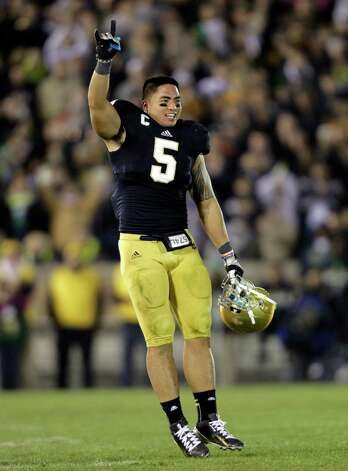 FILE - In this Nov. 17, 2012, file photo, Notre Dame linebacker Manti Te'o acknowledges the applause of fans as he leaves his final home game late in the fourth of an NCAA college football against Wake Forest game in South Bend, Ind. Te'o is a finalist for the Heisman Trophy. (AP Photo/Michael Conroy, FIle) Photo: Michael Conroy