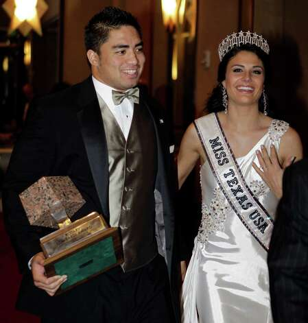 Notre Dame linebacker Manti Te'o is escorted by Miss Texas Ali Nugent as he carries the Lombardi Award to an interview room after a ceremony, Wednesday, Dec. 5, 2012, in Houston. Te'o, also a Heisman Trophy finalist, had 103 tackles and seven interceptions this year to help the undefeated Fighting Irish reach the BCS championship game against Alabama. (AP Photo/Houston Chronicle, Melissa Phillip) Photo: Melissa Phillip