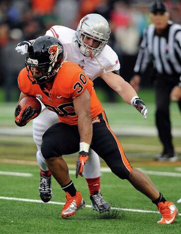Running back Malcolm Agnew #30 of the Oregon State Beavers runs with the ball as linebacker Tyler Harrington #30 of the Nicholls State Colonels pursues in the fourth quarter of the game on December 1, 2012 at Reser Stadium in Corvallis, Oregon. Oregon State won the game 77-3. Photo: Steve Dykes, Getty Images / 2012 Getty Images