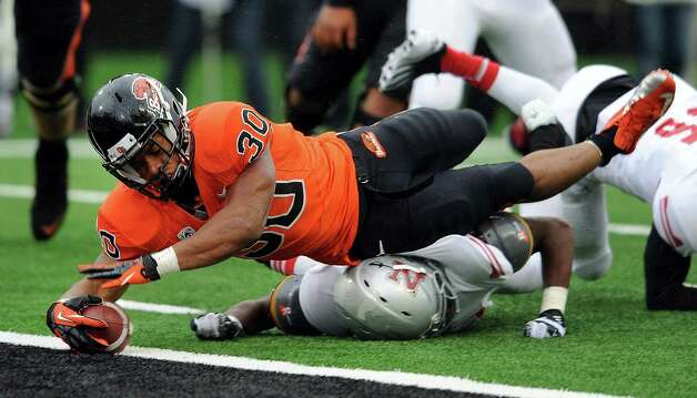 Running back Malcolm Agnew #30 of the Oregon State Beavers dives into the endzone for a touchdown in the fourth quarter of the game against the Nicholls State Colonels on December 1, 2012 at Reser Stadium in Corvallis, Oregon. Oregon State won the game 77-3. Photo: Steve Dykes, Getty Images / 2012 Getty Images