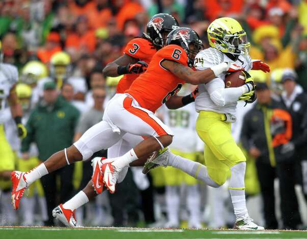 Kenjon Barner #24 of the Oregon Ducks runs against Anthony Watkins #3 and Sean Martin #6 of the Oregon State Beavers during the 116th Civil War on November 24, 2012 at the Reser Stadium in Corvallis, Oregon.  (Photo by Jonathan Ferrey/Getty Images) Photo: Jonathan Ferrey, Associated Press / 2012 Getty Images