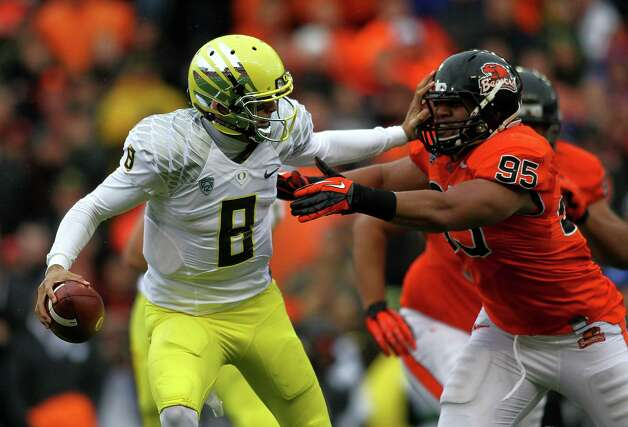 Marcus Mariota #8 of the Oregon Ducks is pressured by Scott Crichton #95 of the Oregon State Beavers during the 116th Civil War on November 24, 2012 at the Reser Stadium in Corvallis, Oregon.  (Photo by Jonathan Ferrey/Getty Images) Photo: Jonathan Ferrey, Associated Press / 2012 Getty Images