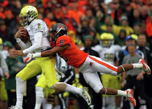 Marcus Mariota #8 of the Oregon Ducks is tackled by Sean Martin #6 of the Oregon State Beavers during the 116th Civil War on November 24, 2012 at the Reser Stadium in Corvallis, Oregon.  (Photo by Jonathan Ferrey/Getty Images) Photo: Jonathan Ferrey, Associated Press / 2012 Getty Images