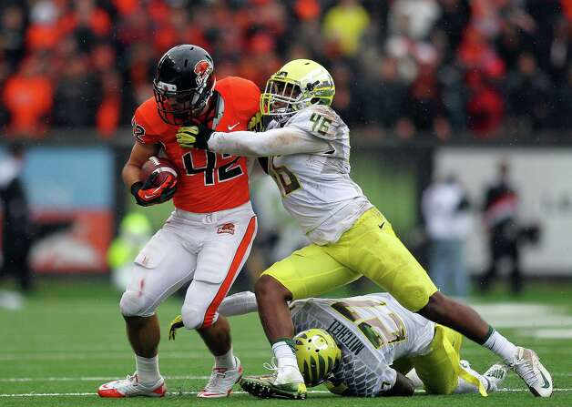 Clayton York #42 of the Oregon State Beavers is tackled by Michael Clay #46 of the Oregon Ducks during the 116th Civil War on November 24, 2012 at the Reser Stadium in Corvallis, Oregon.  (Photo by Jonathan Ferrey/Getty Images) Photo: Jonathan Ferrey, Associated Press / 2012 Getty Images