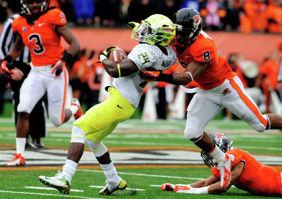 Running back Kenjon Barner #24 of the Oregon Ducks is tackled by safety Tyrequek Zimmerman #8 of the Oregon State Beavers in the first quarter of the game on November 24, 2012 at Reser Stadium in Corvallis, Oregon. (Photo by Steve Dykes/Getty Images) Photo: Steve Dykes, Associated Press / 2012 Getty Images