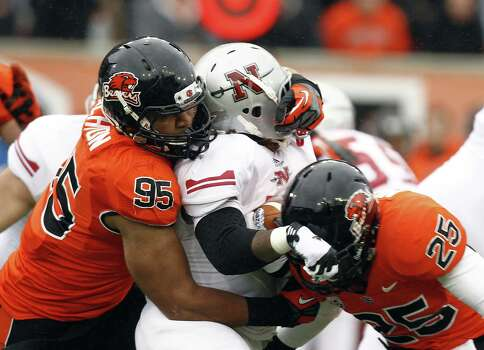 Nicholls State running back Marcus Washington, middle, is wrapped up by Oregon State defenders Scott Crichton, left, and Ryan Murphy during the first half of their NCAA college football game in Corvallis, Ore., Saturday, Dec. 1, 2012. (AP Photo/Don Ryan) Photo: Don Ryan, Associated Press / AP