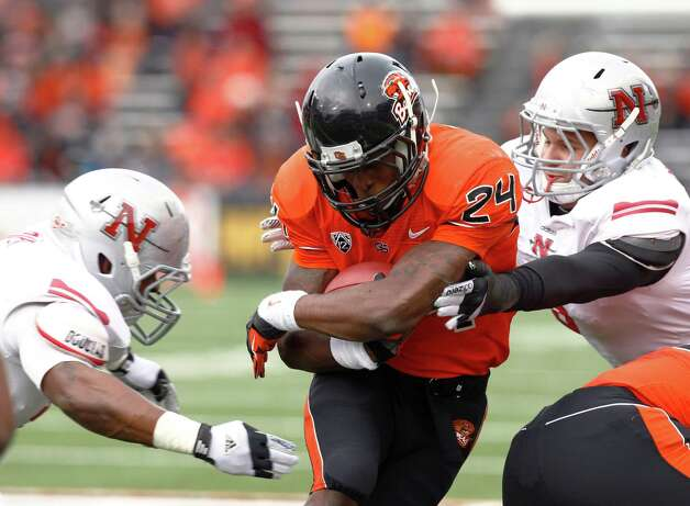Oregon State running back Storm Woods, middle, protects the ball as he runs between Nicholls State defenders B.J. Lewis, left, and Kerry Guidry during the first half of an NCAA college football game in Corvallis, Ore., Saturday, Dec. 1, 2012. Woods ran for two touchdowns in the first quarter and No. 16 Oregon State put up its highest point total ever, routing Nicholls State 77-3 in a game postponed by Hurricane Isaac. (AP Photo/Don Ryan) Photo: Don Ryan, Associated Press / AP