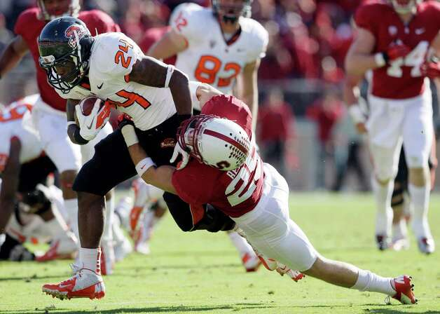 Oregon State running back Storm Woods (24) runs against Stanford cornerback Alex Carter (25) during the second quarter of an NCAA college football game in Stanford, Calif., Saturday, Nov. 10, 2012. (AP Photo/Jeff Chiu) Photo: Jeff Chiu, Associated Press / AP